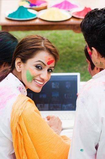Friends celebrating Holi and using a laptop : Stock Photo