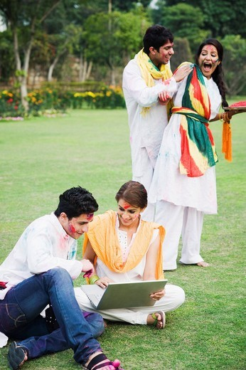 Couple using a laptop with their friends celebrating Holi behind them : Stock Photo