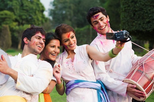 Stock Photo: 1846-12001 Friends taking a picture of themselves with a camera on Holi