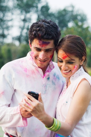 Stock Photo: 1846-12006 Couple text messaging on a mobile phone on Holi