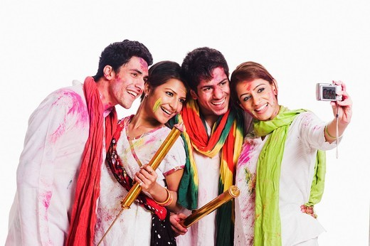 Friends taking a picture of themselves with a camera on Holi : Stock Photo
