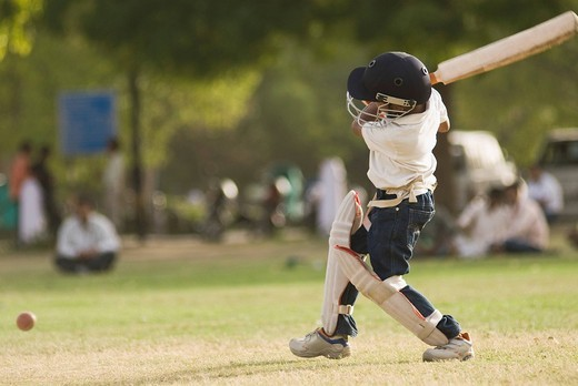 Boy playing cricket in a playground, New Delhi, India : Stock Photo