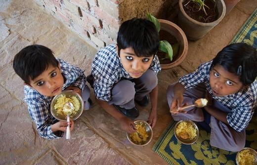 Three school children taking their lunch : Stock Photo