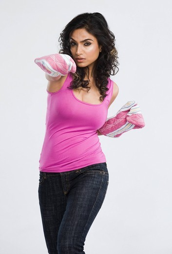 Woman wearing oven mitt and blowing a punch : Stock Photo