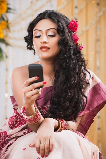 Bride in traditional Bengali dress text messaging on a mobile phone : Stock Photo
