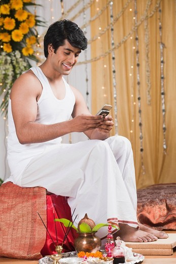 Man text messaging on a mobile phone during Bengali wedding : Stock Photo