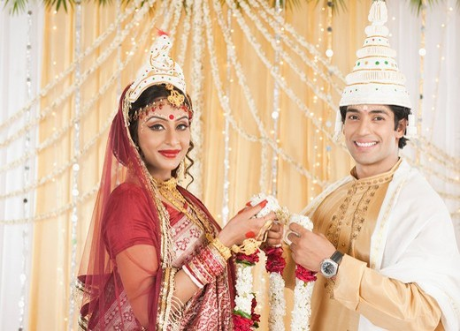 Couple performing Mala Badal Garland Exchanging ceremony in Bengali wedding : Stock Photo