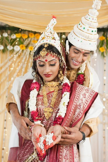 Couple performing Anjali ceremony in Bengali wedding : Stock Photo