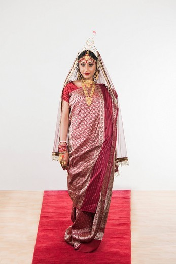 Bride in Bengali dress standing on a carpet : Stock Photo