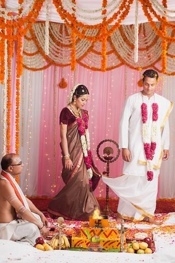 Bride and bridegroom taking Saptha Padhi during South Indian wedding : Stock Photo
