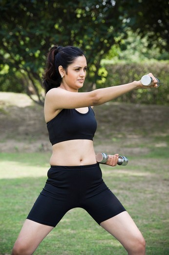 Woman exercising with dumbbells in a park : Stock Photo