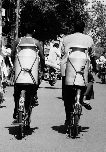 Men carrying milk canisters on bicycles, Agra, Uttar Pradesh, India : Stock Photo