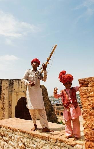 Stock Photo: 1846-13980 Man in traditional Rajasthani dress playing sarangi while a boy dancing, Jaipur, Rajasthan, India