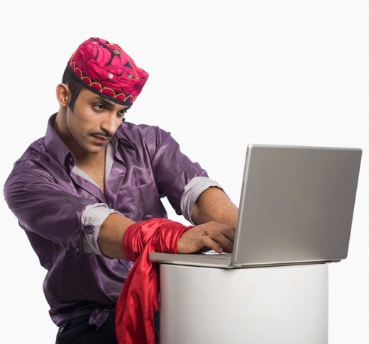 Actor portraying a tapori using a laptop : Stock Photo