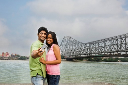Stock Photo: 1846-1780 Couple taking a picture of themselves with a bridge in the background, Howrah Bridge, Hooghly River, Kolkata, West Bengal, India