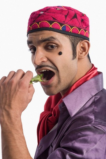 Stock Photo: 1846-1787 Portrait of an actor portraying a tapori eating pan