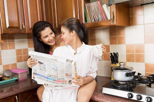 Stock Photo: 1846-2054 Lesbian couple reading a newspaper in the kitchen