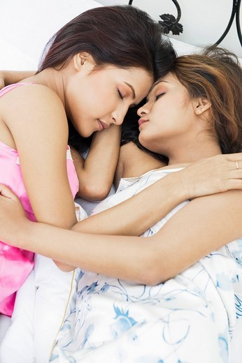 Lesbian couple sleeping on the bed : Stock Photo