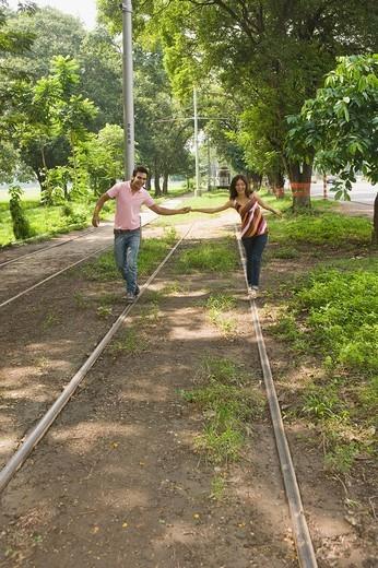 Couple walking on railroad tracks, Kolkata, West Bengal, India : Stock Photo