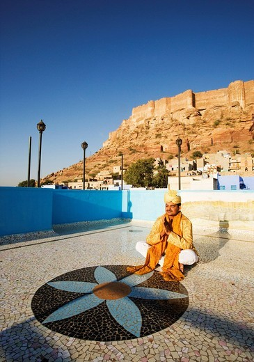 Groom in prayer position with fort in the background, Meherangarh Fort, Jodhpur, Rajasthan, India : Stock Photo