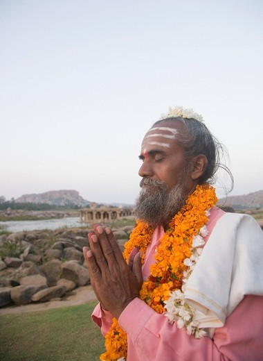 Stock Photo: 1846-4305 Sadhu standing in a prayer position, Hampi, Karnataka, India