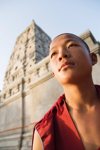 Monk day dreaming in front of a temple, Mahabodhi Temple, Bodhgaya, Gaya, Bihar, India : Stock Photo
