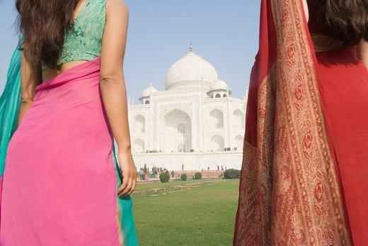 Two women standing in front of a mausoleum, Taj Mahal, Agra, Uttar Pradesh, India : Stock Photo