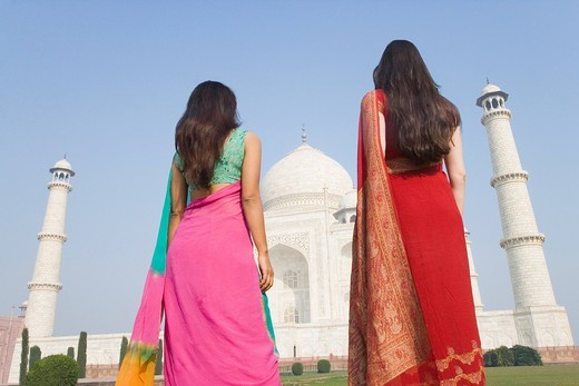 Two women standing in front of a mausoleum, Taj Mahal, Agra, Uttar Pradesh, India : Stock Photo