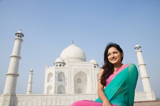 Woman smiling in front of a mausoleum, Taj Mahal, Agra, Uttar Pradesh, India : Stock Photo