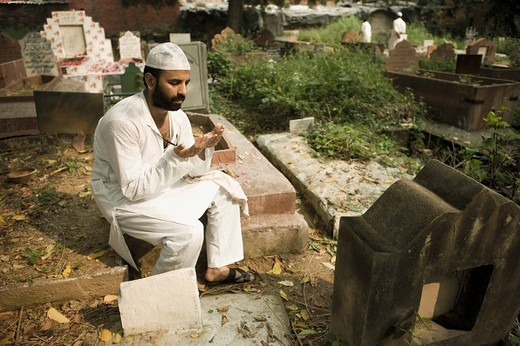 Stock Photo: 1846-6532 Man praying at a grave in a cemetery, Old Delhi, India