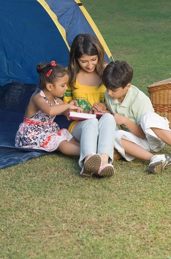 Stock Photo: 1846-6643 Woman reading a book with her children by a tent, New Delhi, India