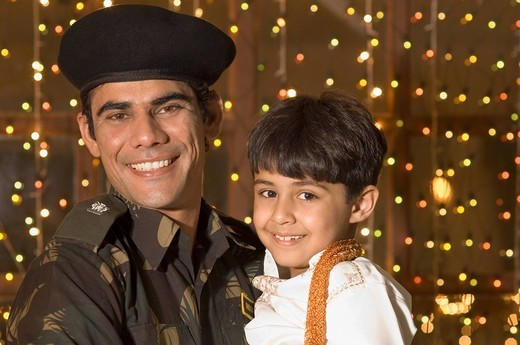 Stock Photo: 1846-6651 Army soldier smiling with his son in front of Diwali decoration
