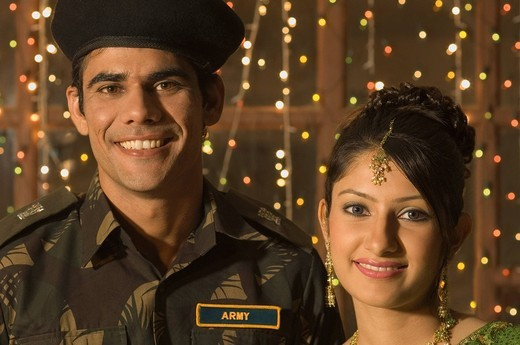 Stock Photo: 1846-6654 Army soldier smiling with a woman in front of Diwali celebration