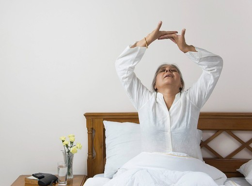 Stock Photo: 1846-6773 Woman stretching on the bed