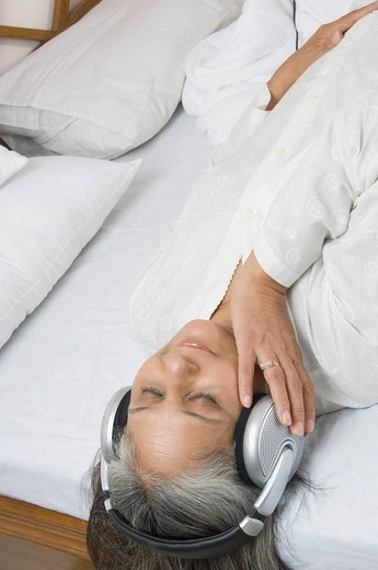 Woman listening to music on the bed : Stock Photo
