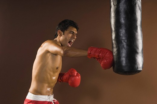 Male boxer showing aggression during practice : Stock Photo