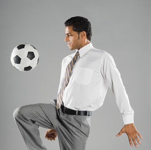 Businessman playing with a soccer ball : Stock Photo