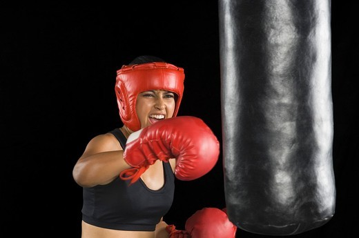 Close_up of a young woman punching on a punching bag : Stock Photo