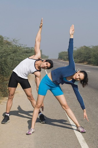 Couple exercising at the roadside : Stock Photo