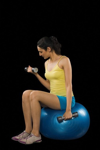 Stock Photo: 1846-7485 Woman exercising with dumbbells on a fitness ball