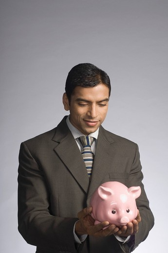 Businessman holding a piggy bank : Stock Photo
