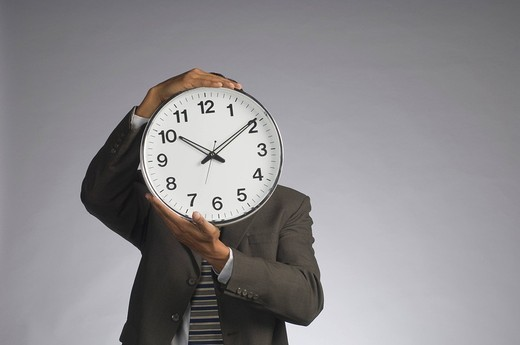 Stock Photo: 1846-7520 Businessman hiding his face with a clock