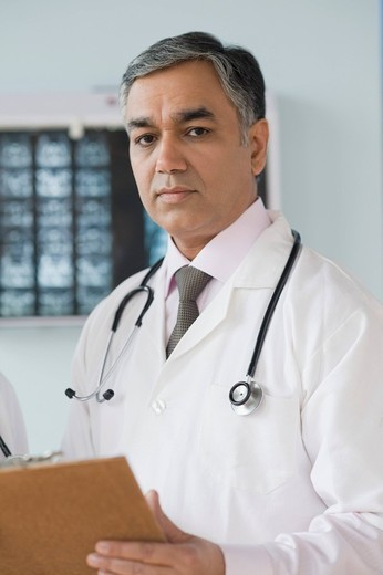 Stock Photo: 1846-7929 Portrait of a doctor holding a clipboard, Gurgaon, Haryana, India