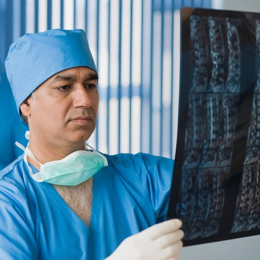 Surgeon examining an x_ray report, Gurgaon, Haryana, India : Stock Photo