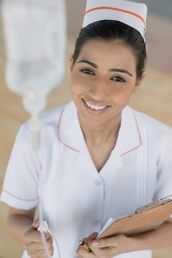 Female nurse adjusting a saline drip, Gurgaon, Haryana, India : Stock Photo