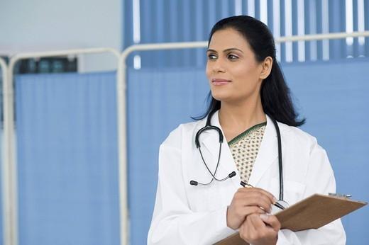 Female doctor writing on a clipboard, Gurgaon, Haryana, India : Stock Photo