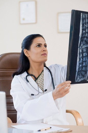 Female doctor examining an x_ray report, Gurgaon, Haryana, India : Stock Photo
