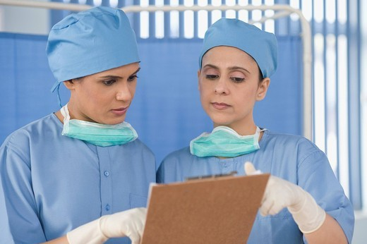 Stock Photo: 1846-8451 Two female surgeons discussing a report, Gurgaon, Haryana, India