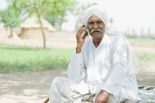 Farmer talking on a mobile phone : Stock Photo