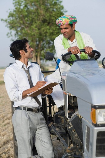 Financial advisor explaining to a farmer about agriculture loan : Stock Photo